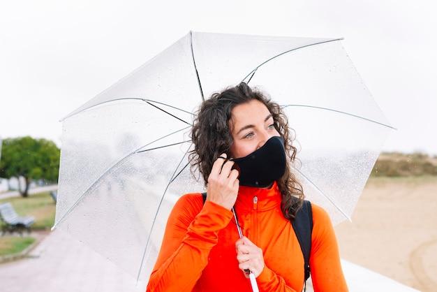 Sportowa kobieta z maską i parasolem w dół ulicy