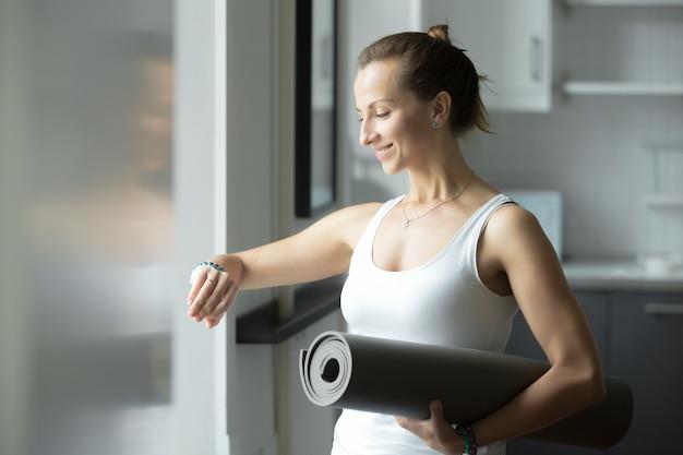 Sportowa kobieta z matą patrząc na jej zegarek
