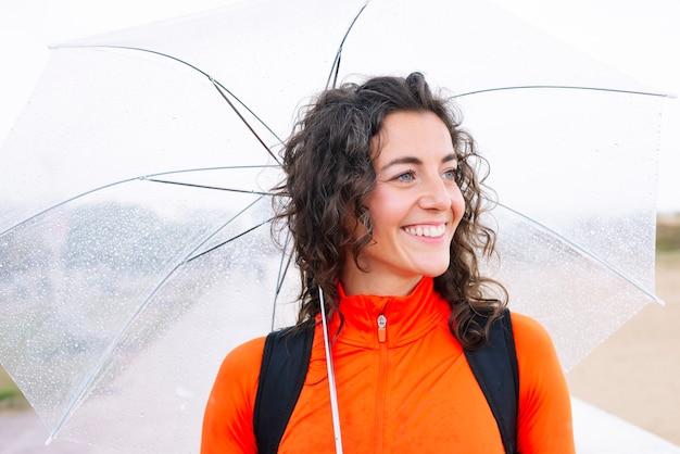 Sportowa kobieta z parasolem w dół ulicy