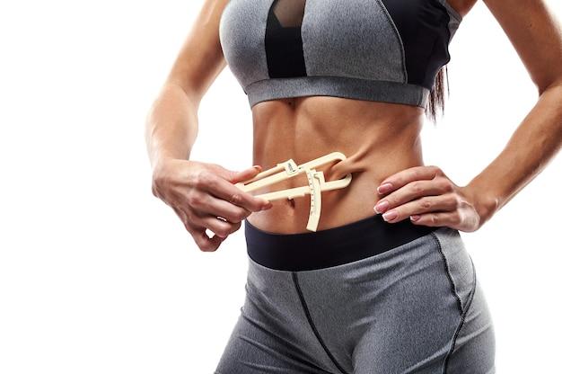 Sportowa kobieta z pięknym brzuchem i płaskim brzuchem za pomocą suwmiarki do pomiaru procentowej zawartości tłuszczu brzusznego w organizmie. ręczna kontrola procentu tłuszczu ketonowego
