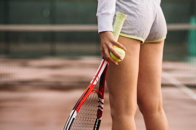 Sportowa kobieta z tenisowym wyposażeniem na tenisowym polu