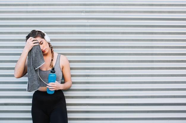 Sportowa kobiety obcierania twarz po treningu