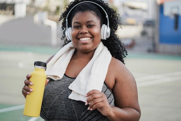 Sportowa krągła czarna kobieta słucha muzyki przez słuchawki - skup się na twarzy