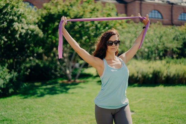 Sportowa ładna kobieta w strojach sportowych ćwiczy z elastyczną gumą z gumy i nosi okulary przeciwsłoneczne w pozach na świeżym powietrzu