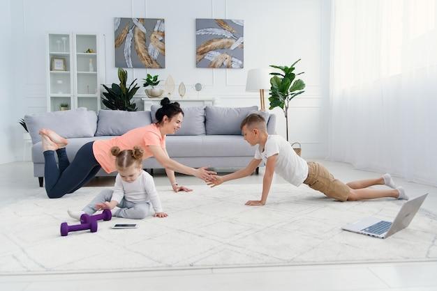 Sportowa mama z synem robi poranny trening w domu, podczas gdy dziecko bawi się