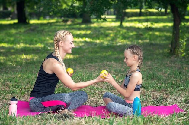 Sportowa matka daje swojemu córce świeże zielone jabłko na maty w parku