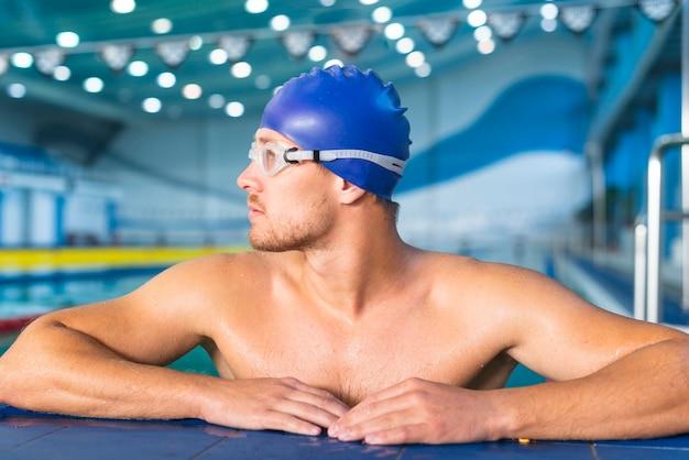 Sportowa męska pływaczka patrzeje daleko od
