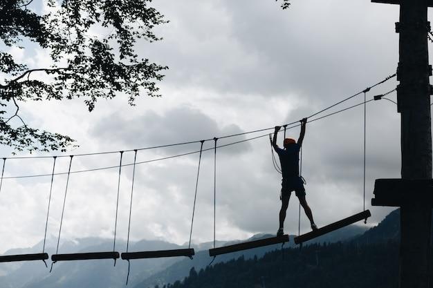 Sportowa męska sylwetka w park linowy w pięknym lesie