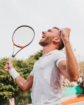 Sportowa młoda chłopiec wygrywa tenisową grę