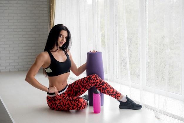 Sportowa młoda dziewczyna z matą fitness i butelką wody. zdrowy tryb życia