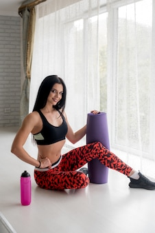 Sportowa młoda dziewczyna z matą fitness i butelką wody. zdrowy tryb życia.