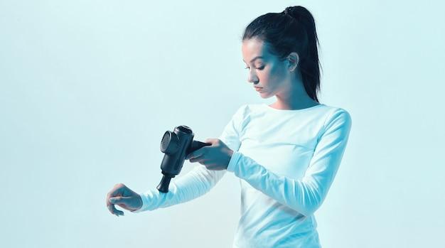 Sportowa młoda kobieta masuje ręcznie ręczny pistolet do masażu w świetle neonu, regeneracja po treningu