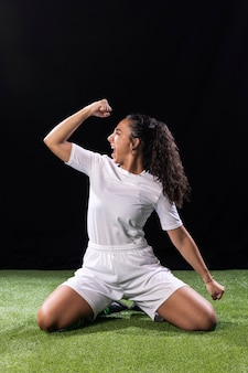 Sportowa młoda kobieta na boisku piłkarskim