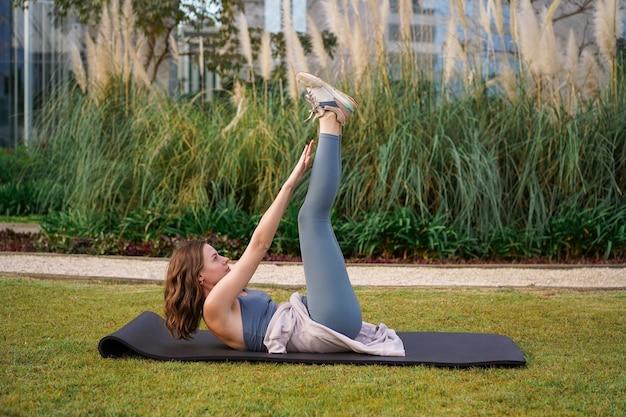 Sportowa młoda kobieta robi ćwiczenia na abs w parku miejskim na świeżym powietrzu