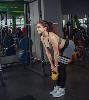 Sportowa młoda kobieta robi ćwiczenia z kettlebell na siłowni. wolne ciężary, trening funkcjonalny
