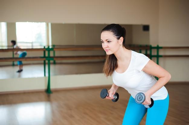 Sportowa młoda kobieta robi ćwiczeniom z dumbbells w gym.