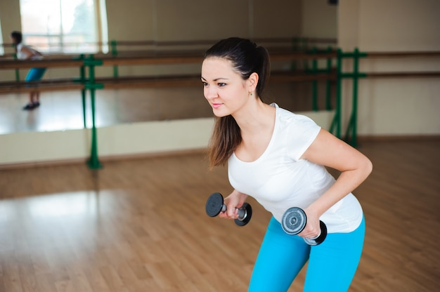 Sportowa młoda kobieta robi ćwiczeniom z dumbbells w gym