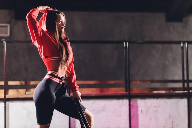 Sportowa młoda kobieta robi niektóre ćwiczy z arkaną plenerową.
