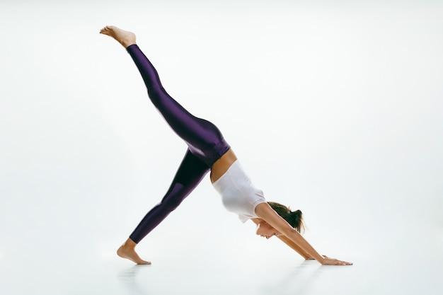 Sportowa młoda kobieta robi praktykę jogi na białym tle. dopasuj elastyczny model ćwiczący. pojęcie zdrowego stylu życia i naturalnej równowagi między ciałem a rozwojem umysłowym.