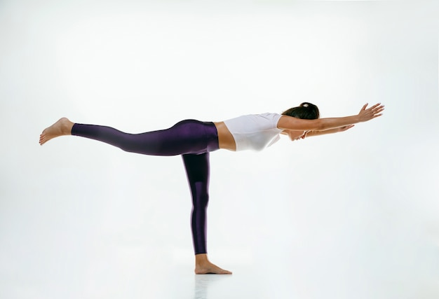 Sportowa młoda kobieta robi praktykę jogi na białym tle. dopasuj elastyczny model ćwiczący