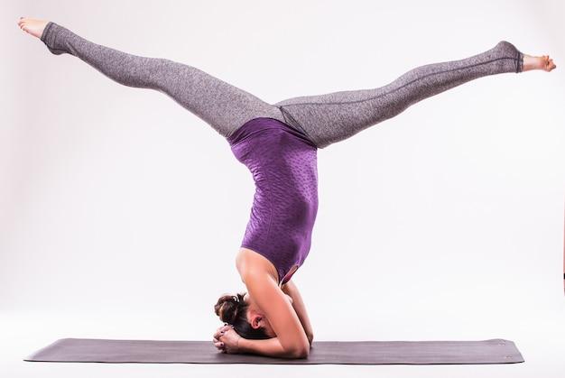 Sportowa młoda kobieta robi praktykę jogi na białym tle - koncepcja zdrowego życia i naturalnej równowagi między ciałem a rozwojem umysłowym