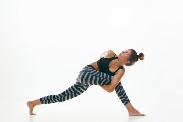 Sportowa młoda kobieta robi praktykę jogi na białym tle na tle białego studia. dopasuj elastyczny model ćwiczący. pojęcie zdrowego stylu życia i naturalnej równowagi między ciałem a rozwojem umysłowym.