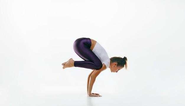 Sportowa młoda kobieta robi praktykę jogi na białym tle