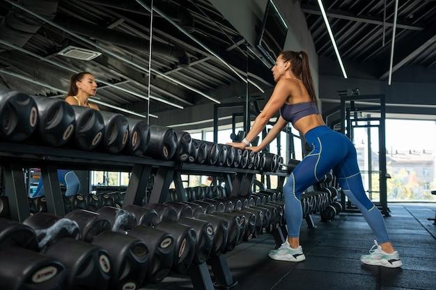 Sportowa młoda kobieta stojąca w pobliżu lustra na stojaku na hantle w siłowni