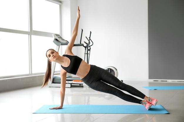 Sportowa młoda kobieta trenuje na siłowni