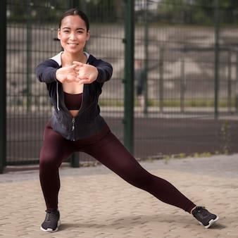Sportowa młoda kobieta trenuje outdoors