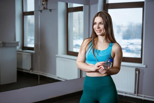 Sportowa młoda kobieta trzyma butelkę wody na siłowni przez lustro