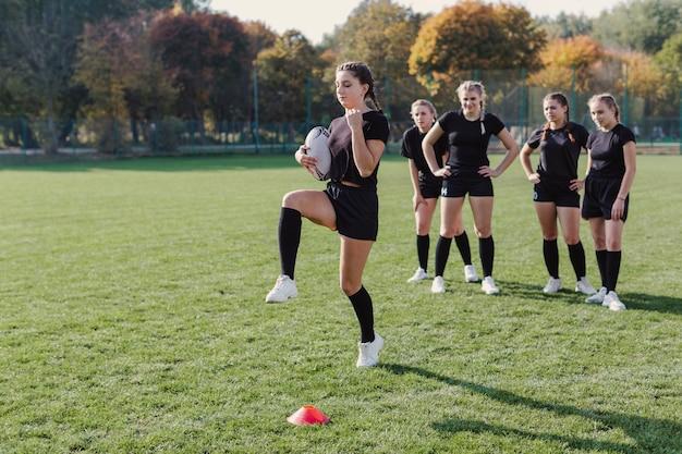 Sportowa młoda kobieta trzyma piłki nożnej piłkę