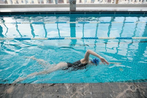 Sportowa młoda kobieta w czapce pływanie skok sam w nowoczesnym basenie z czystą wodą