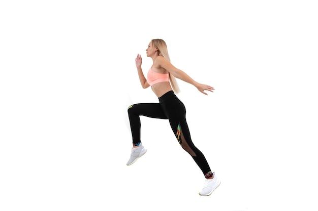 Sportowa młoda kobieta w różowej bluzce, legginsach i trampkach biegnie do przodu