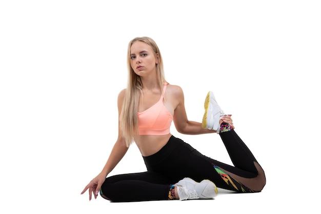 Sportowa młoda kobieta w różowy top, legginsy i trampki pozowanie