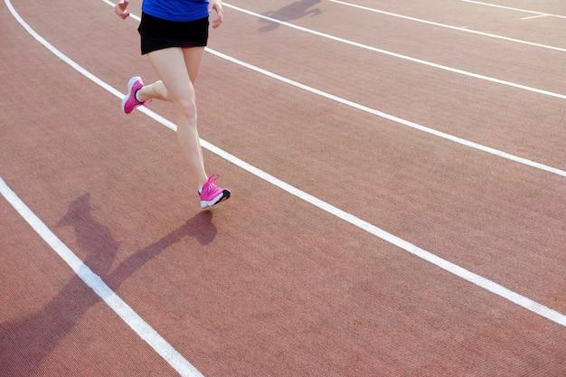 Sportowa młoda kobieta w różowych sneakers biega na bieg śladu stadium