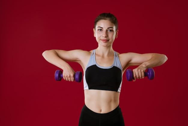 Sportowa młoda kobieta w sportowej z hantlami w ręku na czerwoną kobietę idzie do sportu