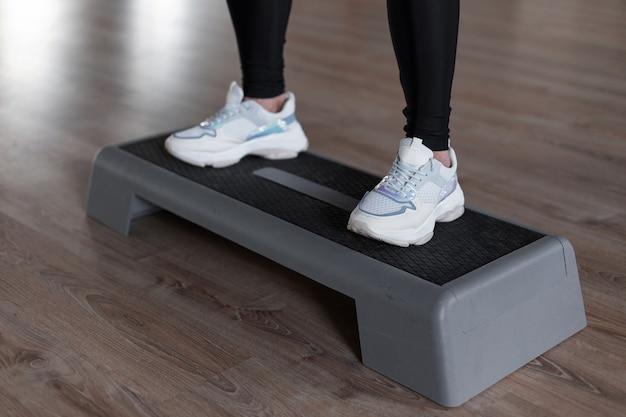 Sportowa młoda kobieta w stylowych białych trampkach w leginsach kuca na schodach platformy w siłowni