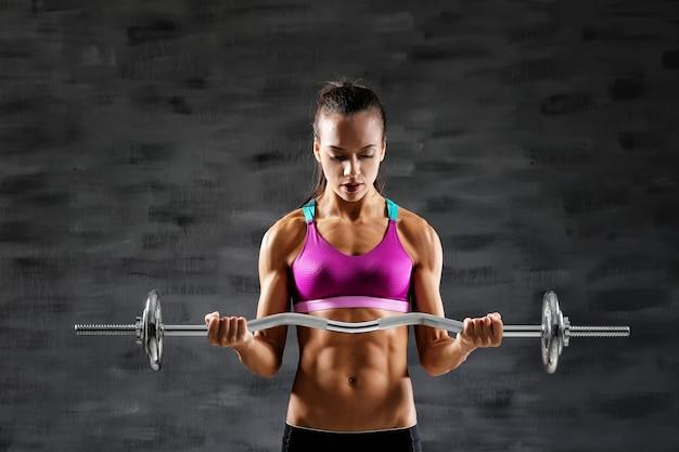 Sportowa młoda kobieta ze sztangą na szaro