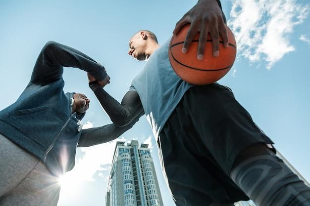 Sportowa młodzież. niski kąt miłego młodzieńca trzymającego piłkę podczas witania przyjaciela