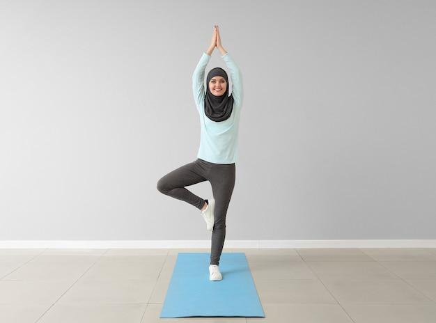 Sportowa muzułmanka praktykuje jogę na siłowni