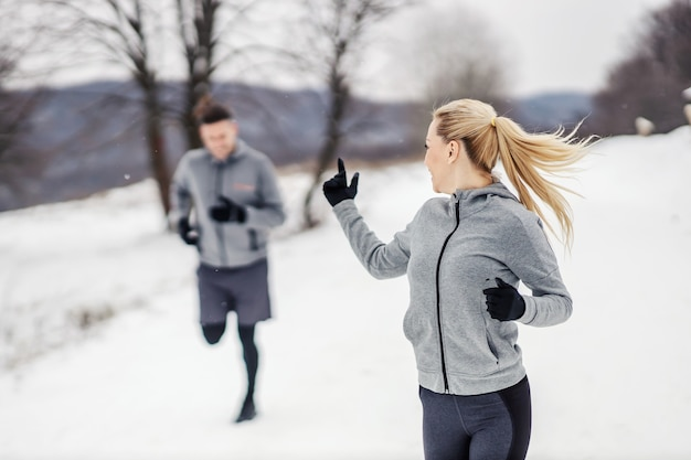 Sportowa para działa razem w przyrodzie w zimowy dzień na śniegu.