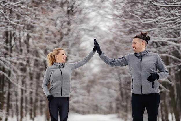 Sportowa para działa razem w śnieżny zimowy dzień w lesie.