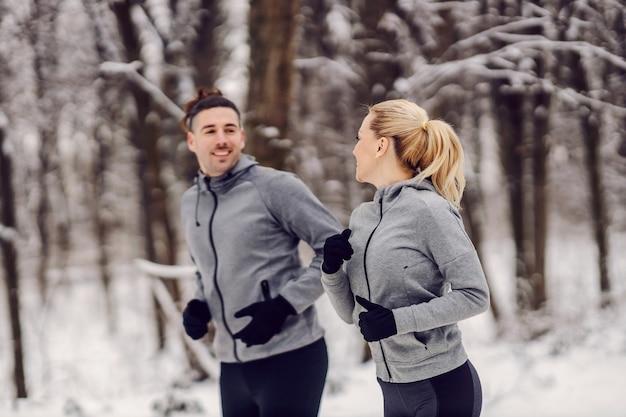 Sportowa para jogging razem w lesie w mroźny zimowy dzień. związek, fitness na świeżym powietrzu, zdrowe życie