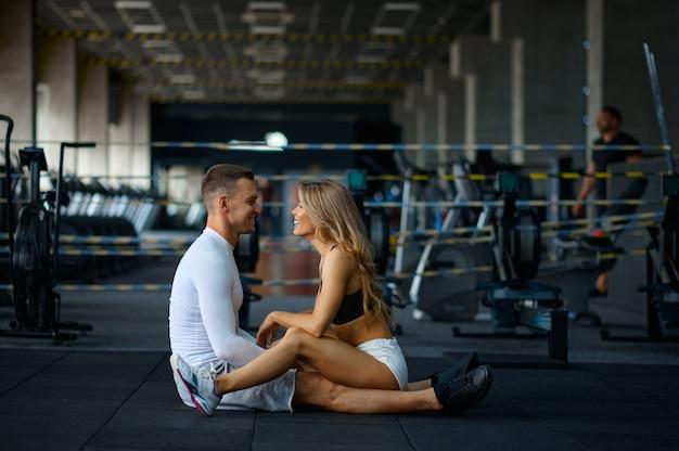 Sportowa para miłości siedząca na podłodze, trenująca w siłowni