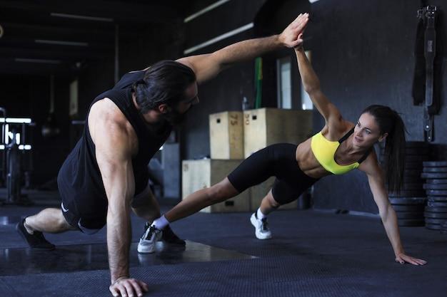 Sportowa para robi pompki i przybija piątkę na siłowni.