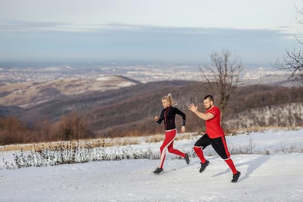 Sportowa para ściga się w przyrodzie w śnieżny zimowy dzień.