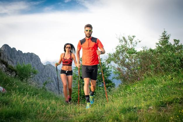 Sportowa para w górach z kijkami do nordic walking