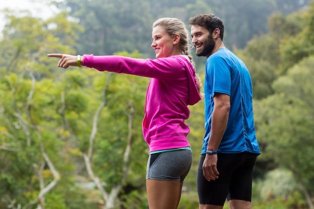 Sportowa para wskazuje przy naturą
