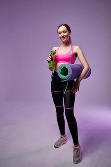 Sportowa piękna kobieta w sportowej, trzymając butelkę wody i fitness mat na białym tle na fioletowo. iść na siłownię.
